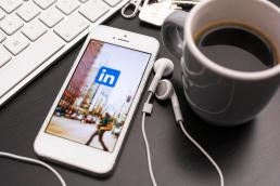 linkedin on mobile phone with headphones and cofee