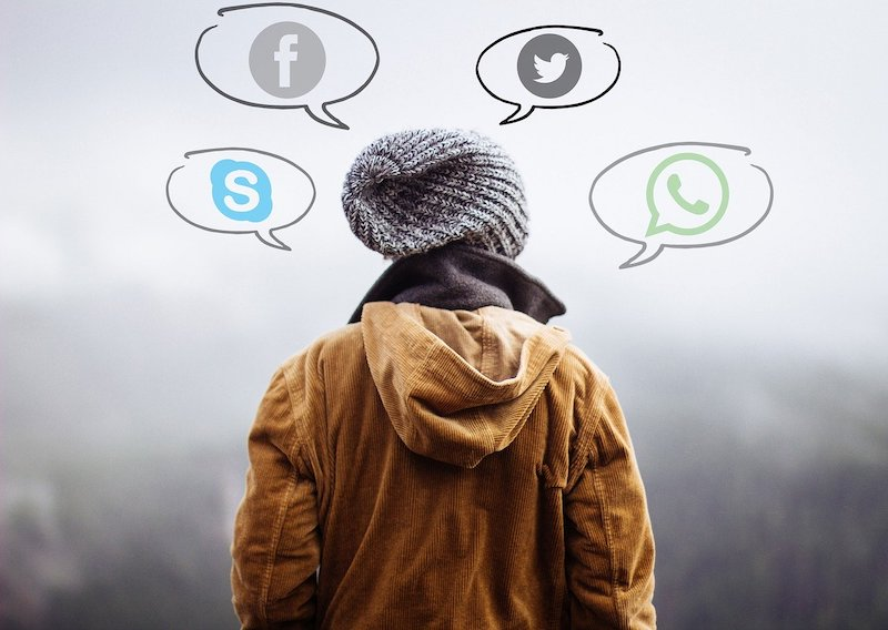 a person with a beanie and thought bubbles with social media icons